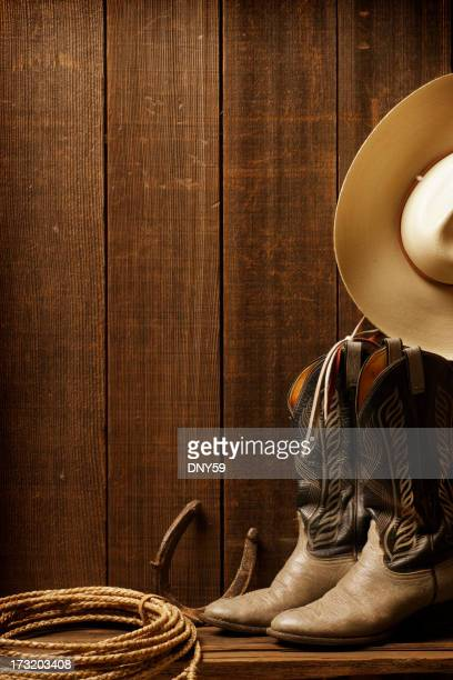 Cowboy boots, a cowboy hat, and lasso against barn