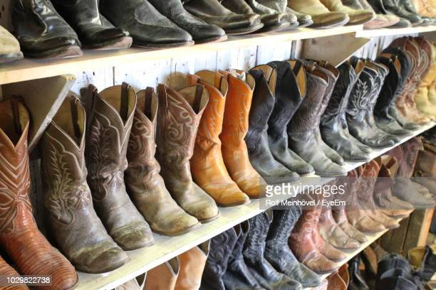 cowboy boots arranged on shelves in store - leather boot stock pictures, royalty-free photos & images