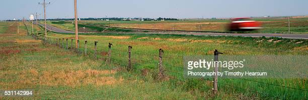 cowboy boots on fence posts; red vehicle passing on road - timothy hearsum stock pictures, royalty-free photos & images