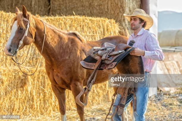 Cowboy carries his saddle after taking it off his horse after a ride