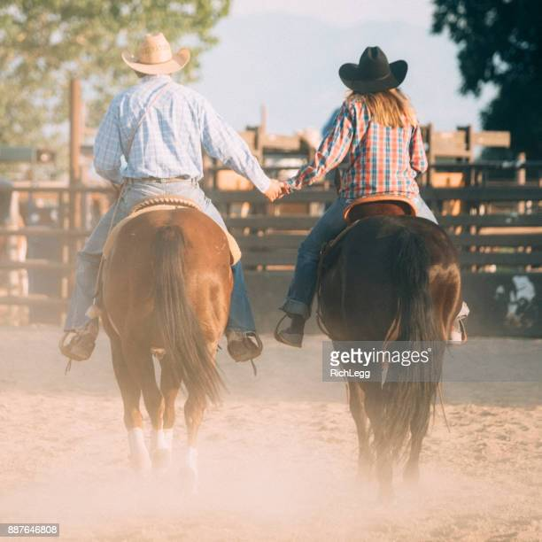 cowboy couple holding hands - rich_legg stock photos and pictures