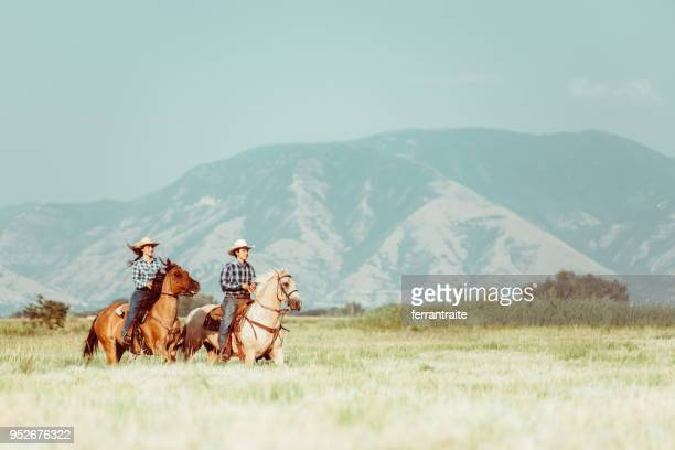 cowboy couple horseback riding - ranch stock pictures, royalty-free photos & images