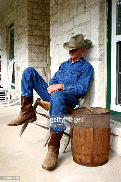 Cowboy dozing in old chair on porch nail keg table