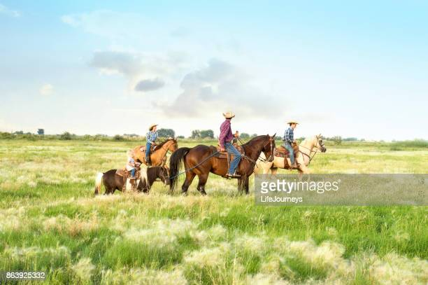 Cowboy Family Out For A Leisure Ride In The Meadows