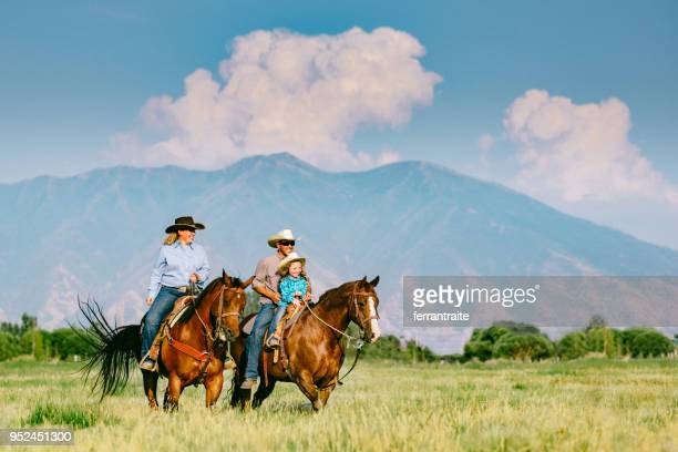 cowboy family riding horses together - cowboy stock photos and pictures