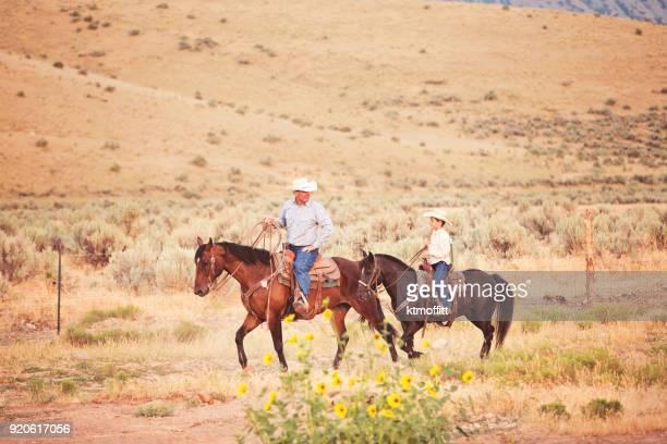 カウボーイの父と息子の日の終わりに一緒に乗って