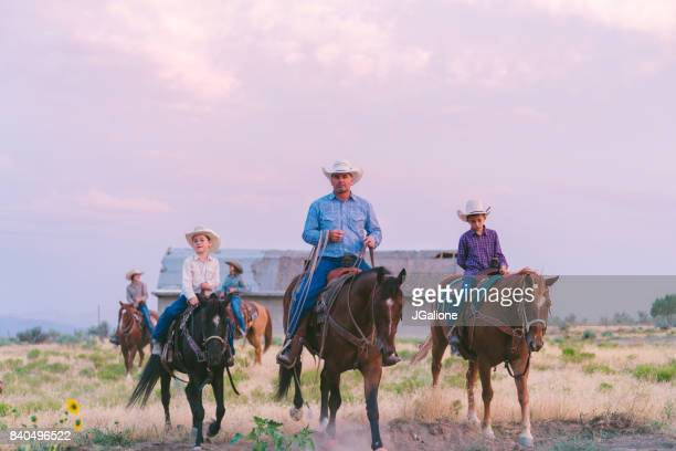 Cowboy father and sons at sunset