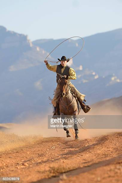 Cowboy galloping with lasso in hand