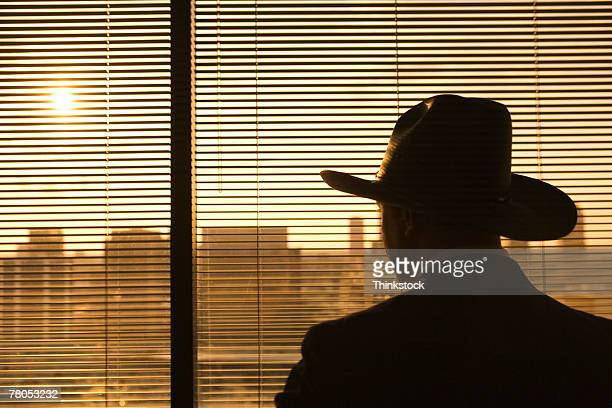 Cowboy gazing at cityscape out window