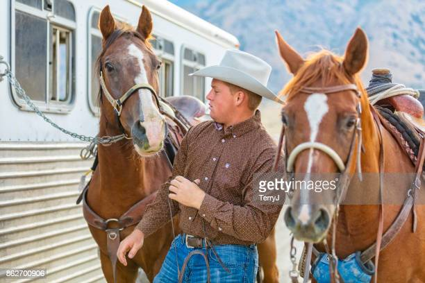 cowboy gets ready to put a bridle on his horse to go for a ride - sorrell booke foto e immagini stock