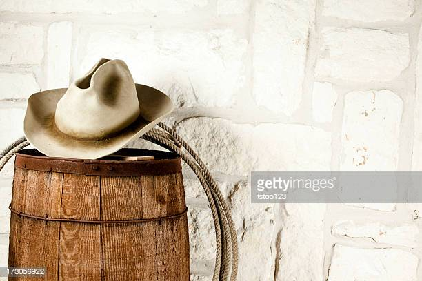 Cowboy hat and lasso on barrel. Austin sandstone background