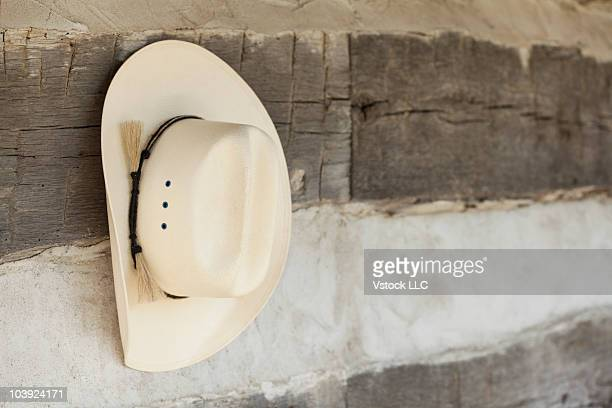 Cowboy hat hanging on wall of log cabin