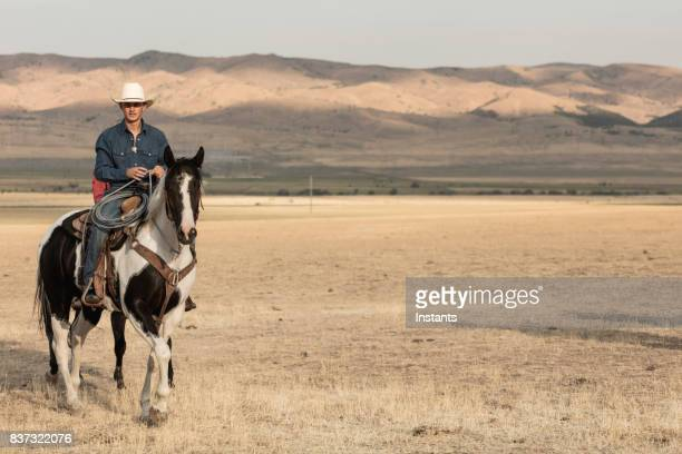 A cowboy, holding a lasso, horseback riding on a ranch.