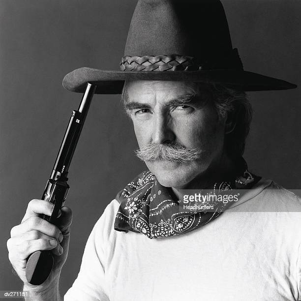 cowboy holding gun to hat - headhunters stock pictures, royalty-free photos & images