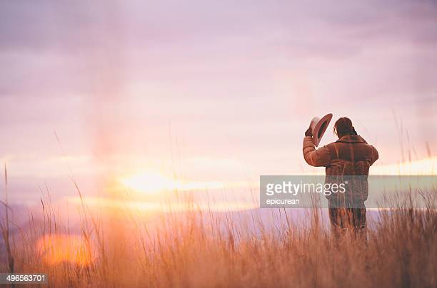 Cowboy holds hat while standing in hay looking at sunset
