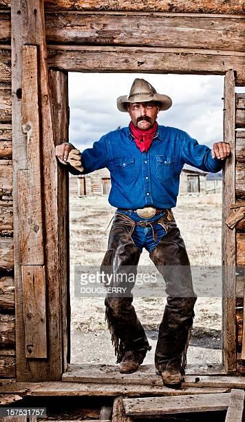 vaquero en puerta - pantalón de cuero fotografías e imágenes de stock