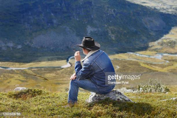 cowboy in mountains - ダブルデニム ストックフォトと画像