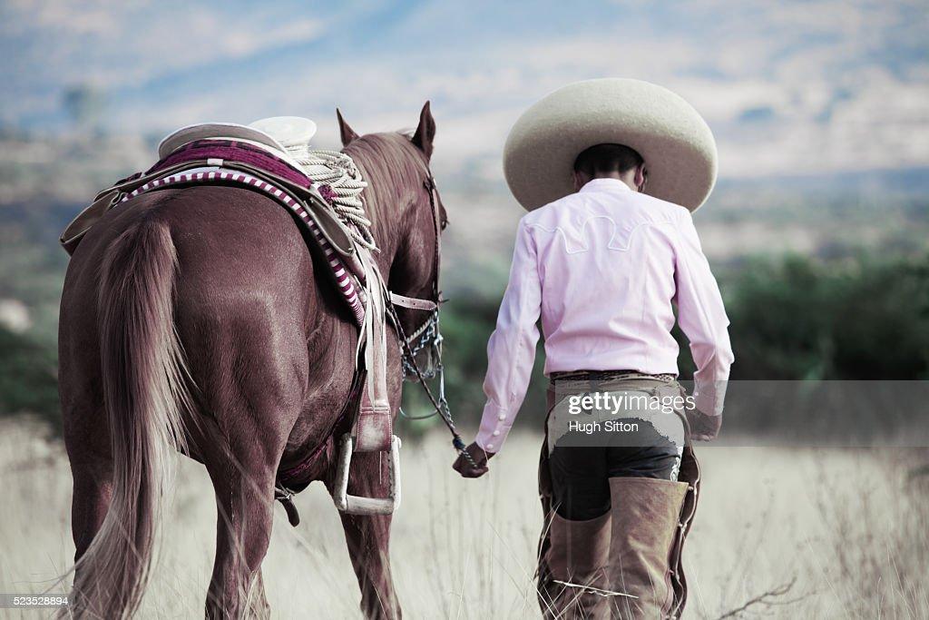 Cowboy leading horse : Stock Photo
