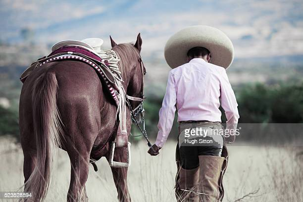 cowboy leading horse - hugh sitton stock pictures, royalty-free photos & images