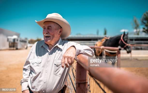 cowboy leunend op een hek en lasso in rodeo arena houden - cowboy stockfoto's en -beelden