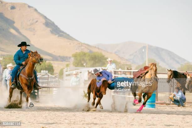 Cowboy von seinem Pferd springen zu einem Steer Ringen