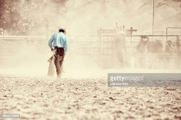 caubói fazendo a caminhada de volta para os para-quedas depois de um passeio de bronc sela bem sucedida - estadio de los cowboys - fotografias e filmes do acervo