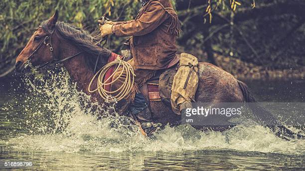 Cowboy on a horse riding across a river