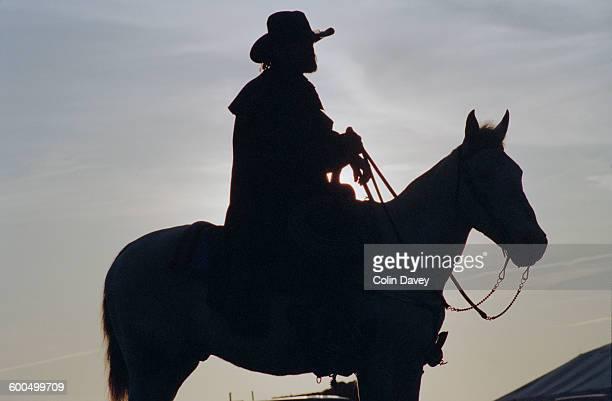 A cowboy on horseback in silhouette USA circa 1990