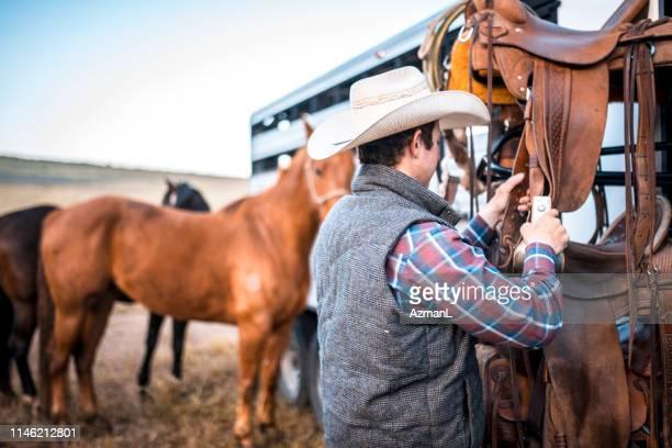 カウボーイはトレーラーに縛ら馬を鞍に準備 - 手綱 ストックフォトと画像