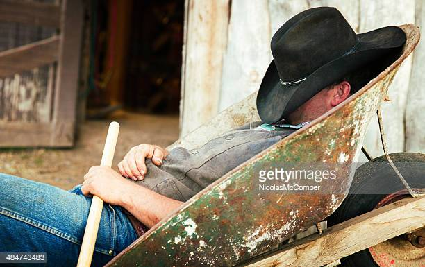 Cowboy resting in wheelbarrow face covered by hat