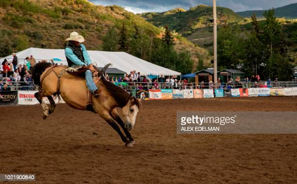 TOPSHOT A cowboy rides a bucking bronco at the Snowmass Rodeo on August 22 in Snowmass Colorado The Snowmass rodeo is on its 45th year making it one...