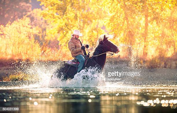 Cowboy rides horse through river on beautiful sunny fall morning