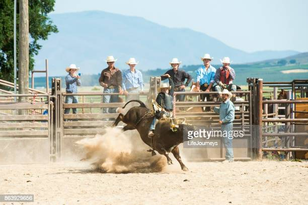Cowboy Riding A Big Thundering Bull In A Rodeo Arena