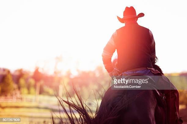 cowboy riding away rear view - paard paardachtigen stockfoto's en -beelden