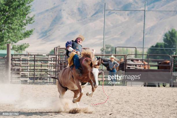 Cowboy riding bareback on a bucking horse