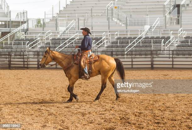 cowboy riding horse at rodeo paddock