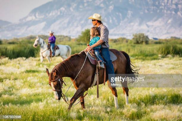 Cowboy riding with his little daughter