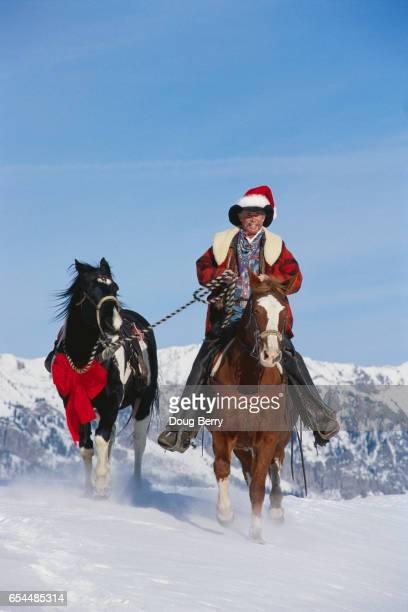 cowboy santa bringing gift horse - cowboy christmas stock pictures, royalty-free photos & images