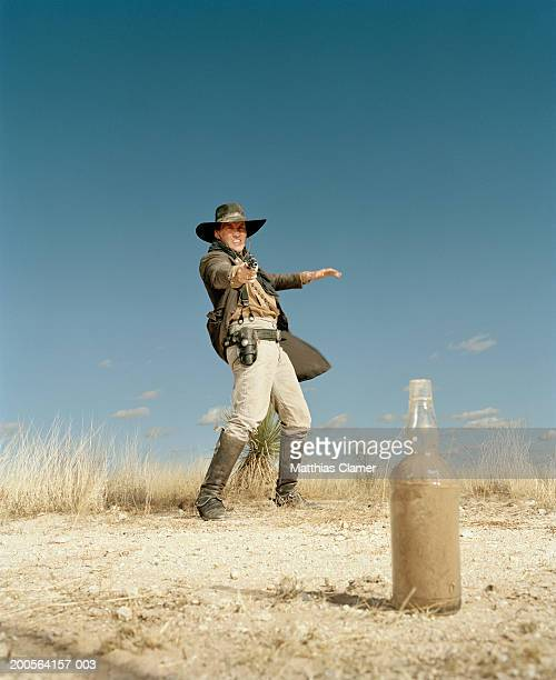 cowboy shooting an empty bottle - cowboy foto e immagini stock