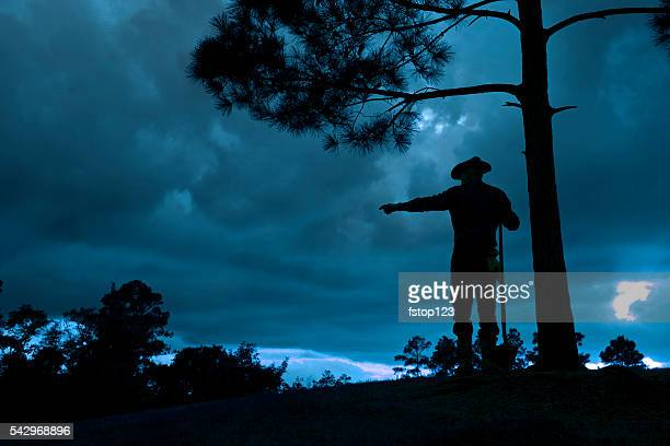 Cowboy: Silhouette rancher, farmer overlooking field after rainstorm at sunset.