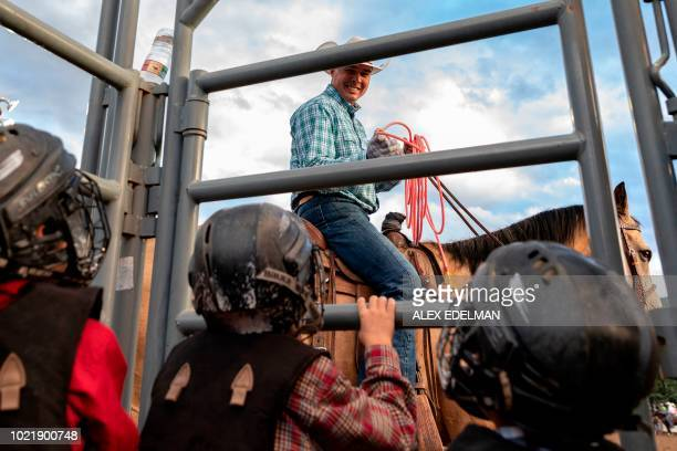 A cowboy smiles at children as they prepare for the mutton bustin' event at the Snowmass Rodeo on August 22 in Snowmass Colorado The Snowmass rodeo...