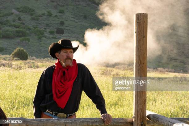 A Cowboy Standing By A Fence With Smoke From A Campfire In The Distance