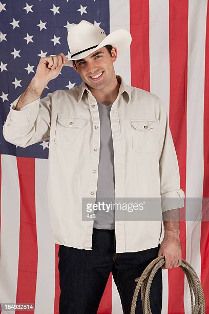 Cowboy standing in front of an american flag