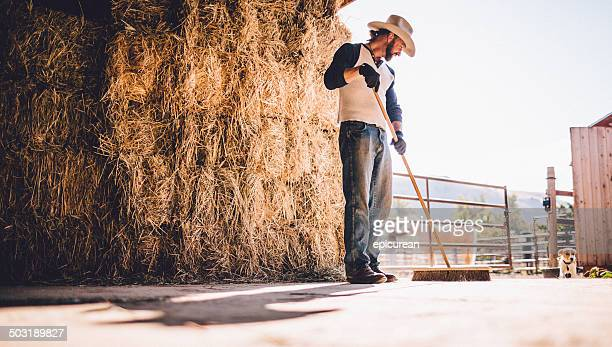 Cowboy sweeps barn while standing in front of haystack