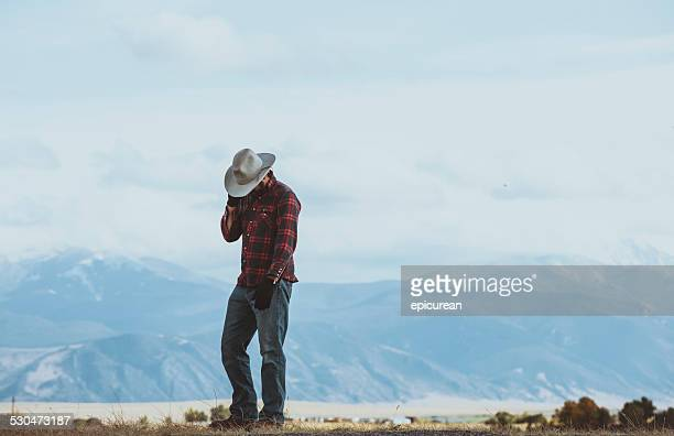 Cowboy talks on phone while standing with mountains in distance