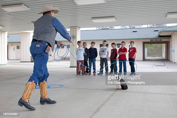 Cowboy teaching boys how to rope cows using a stuffed penguin.