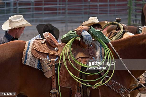Cowboy waiting for calf roping event, with his hands over the saddle and holding his rope. Horse, rope, cowboy hats and saddle.