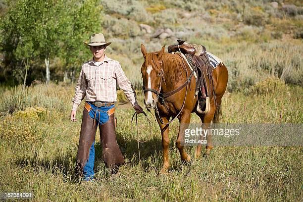 cowboy pasos con su caballo - pantalón de cuero fotografías e imágenes de stock