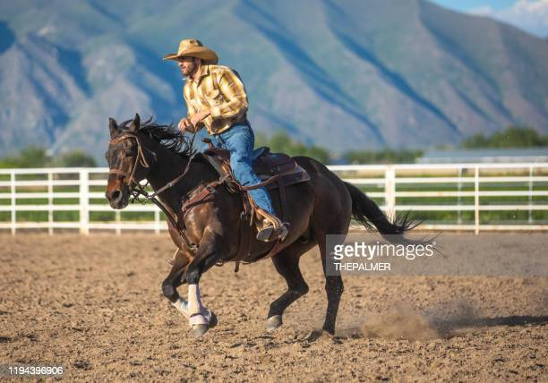 cowboy warming up before event at a rodeo arena - riding stock pictures, royalty-free photos & images