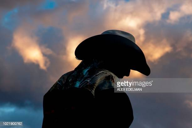 TOPSHOT A cowboy watches the rodeo from behind the chute at the Snowmass Rodeo on August 22 in Snowmass Colorado The Snowmass rodeo is on its 45th...